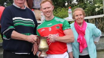 Adrian O'Dwyer of Cashel King Cormacs receives the Jamesie O'Donoghue Cup from West Board Chairman Michael Ryan C, in the presence of Jamesie's mother Una O'Donoghue